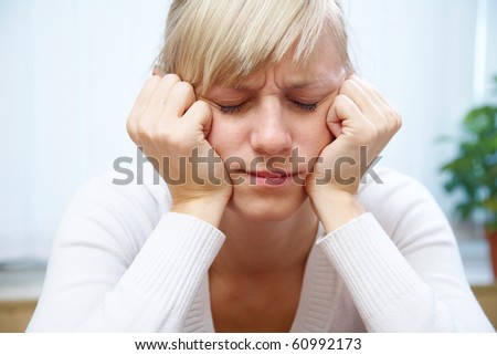 young white woman sadly sitting with his head propped on his hands and his eyes closed
