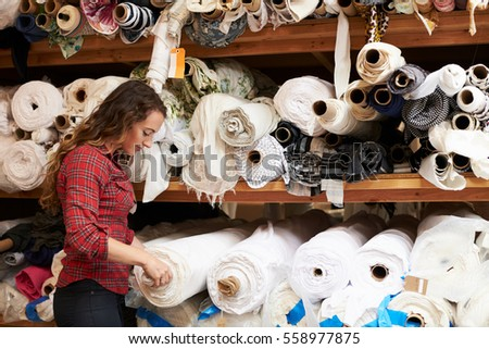 Young white woman selects fabric at a clothing design studio