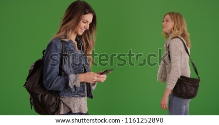 Young white woman using smartphone while her friend looks around on green screen stock photo
