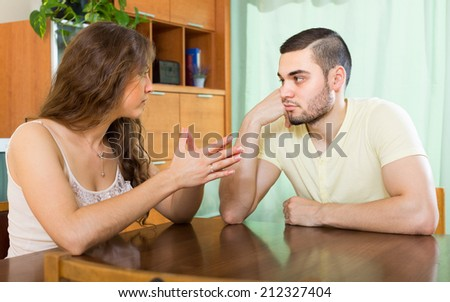 Young wife and husband having serious talking at the table in home #212327404