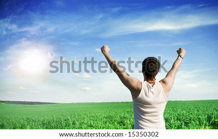 Young winner man looking at blue sky with clouds