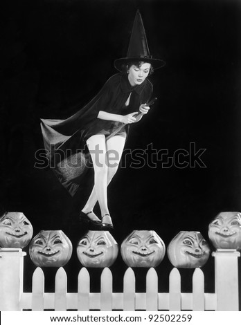 Young witch hovers on her broom, eyeing which pumpkin to choose