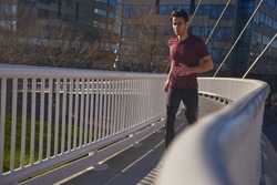 Young with dark hair is running along a path on a bridge with buildings in the background