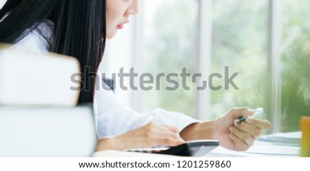 Young woman account manager working seriously with calculator in office desk #1201259860