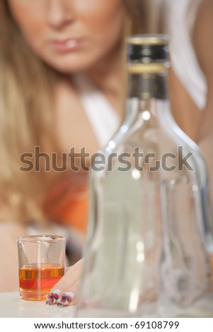 Young woman addicted to alcohol - focus on glass