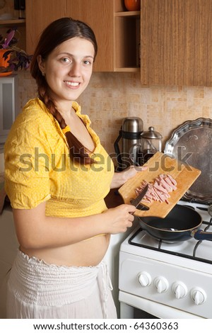 Young woman adds sliced bacon to hot skillet. One of the stages of preparation of bacon and eggs.  See series