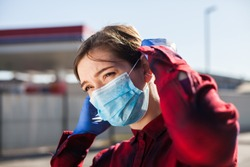 Young woman adjusting protective face mask,standing on petrol station parking lot, Coronavirus COVID-19 corona virus disease global pandemic outbreak crisis, people wearing medical equipment in public
