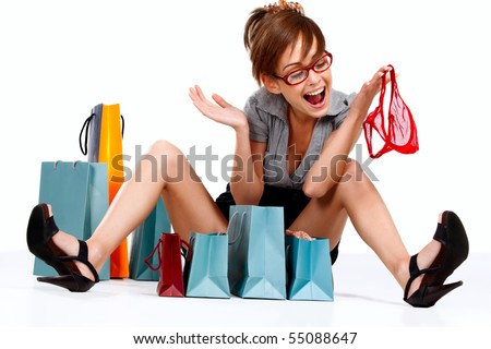 Young woman admiring her shopping getting red lingerie out of the shopping bag