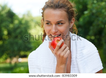 Young woman after sport workout eating apple - stock photo