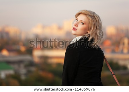 Young woman against autumn urban background