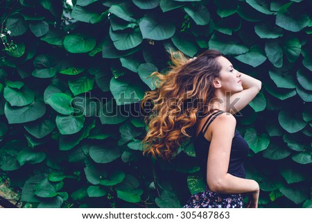young woman, against background of summer green park, green leaves. Running girl with beautiful curly hair