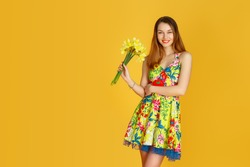 Young woman against yellow wall with flowers in hand in studio