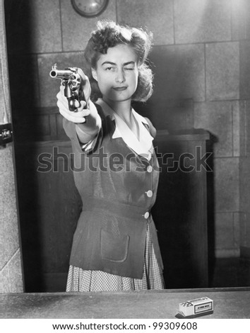 Young woman aiming with a handgun