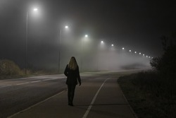Young woman alone slowly walking under white street lights in night. Dark time. Peaceful atmosphere in mist. Foggy air. Back view.