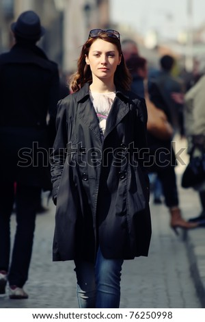 Young woman among human rush in the city