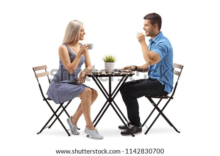 Young woman and a young man sitting at a coffee table isolated on white background