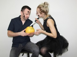 young woman and attractive man carving or cutting halloween pumpkin in costumes for party. celebrating halloween in 2020 at home quarantine. situation caused by coronavirus.