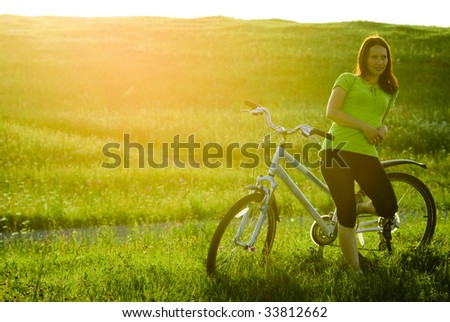Young woman and blue bicycle at sunset.