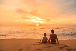 Young woman and boy, mother and son sitting on the beach at sunset, Kalutara, Sri Lanka
