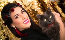 Young woman and cute cat with gold background
