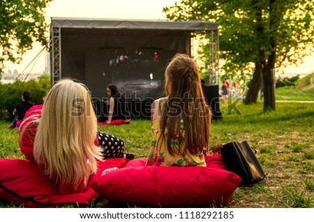 Young woman and girl laying cozy on pillow i green grass and watching film in open cinema in public green park.Back of twofemale in nature enjoying movie on big screen - Shutterstock ID 1118292185
