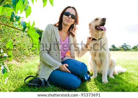 Young woman and golden retriever sitting in the grass|