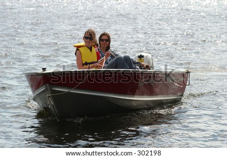 Young woman and her daughter in a motor boat,