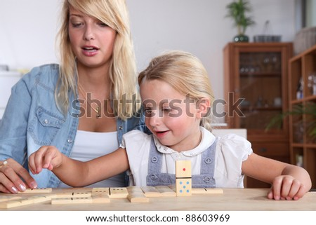 Young woman and her daughter playing dominoes