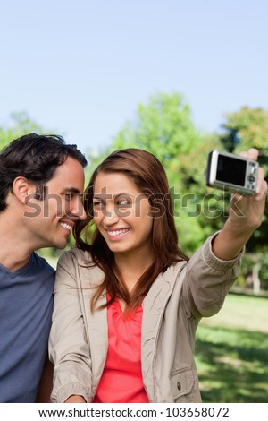 Young woman and her friend look at each other while she takes a photo of them together using her camera