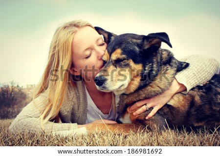 Young woman and her German Shepherd dog lying in the grass, she is hugging and kissing him. Vintage style color.