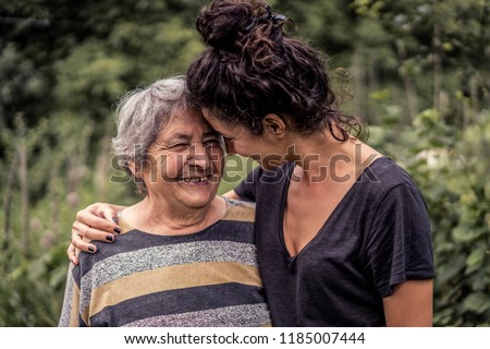 Young woman and her grandmother, very old woman. Two generations. Family love.