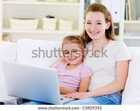 Young woman and her little daughter with laptop - indoors