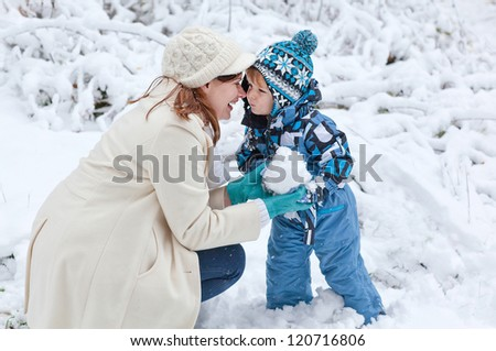 Young woman and her little son having fun with snow outdoors on beautiful winter day