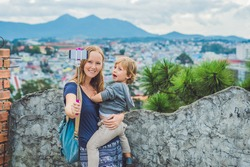 Young woman and her son taking smart phone self portrait pictures with selfie stickon the background of the city of Dalat, Vietnam.