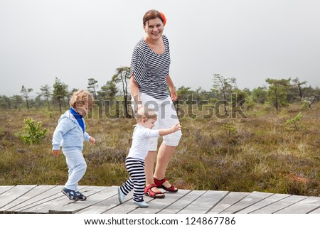 Young woman and her two little toddler boys walking through nature park in summer