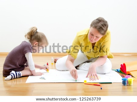 Young woman and little girl drawing together sitting on the floor