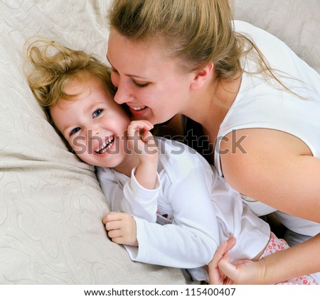 Young woman and little girl having fun in bed