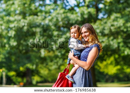 Young woman and little girl of one year walking through summer park