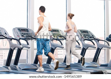 Young woman and man at the gym exercising Run on a machine