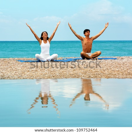 Young Woman and Man Doing Yoga at Sea and Reflected in Water