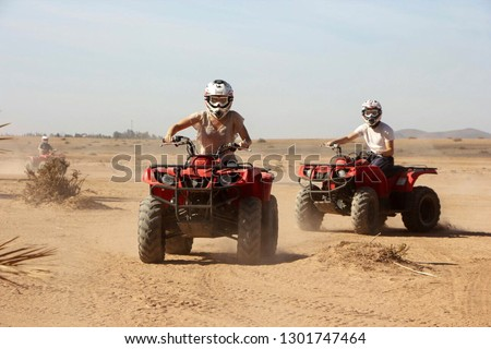 Young woman and man driving Quadbikes in desert area outside of Marrakech, Morocco Stock photo ©