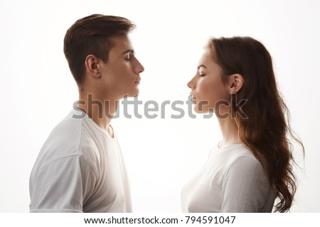 Young woman and man in love standing with closed eyes. Love is in the air, those who jealous, try not to breathe. They do not care about the rest, because in their universe only two of them exist.