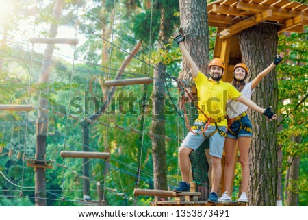 Young woman and man in protective gear are standing on wooden board on high tree, posing and smiling. Rope adventure park with obstacles and ziplines. Extreme rest and summer activities concept.  #1353873491