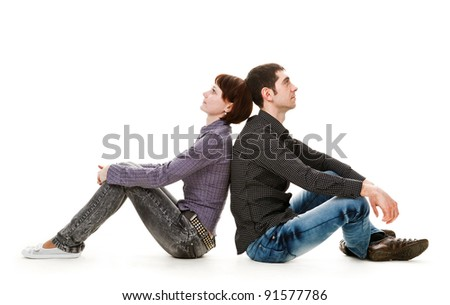 Young woman and man sitting on the floor, back to back, isolated on white background.