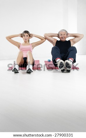 young woman and senior man doing abs in gym