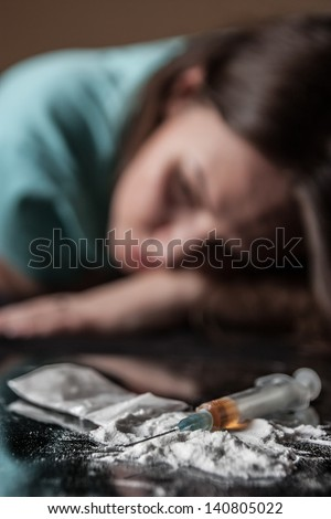 Young woman and syringe with heroin on table