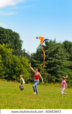 Young woman and two children flying a kite