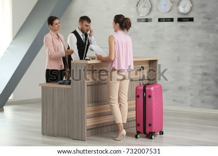 Young woman and two receptionists in hotel #732007531