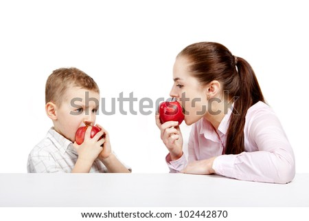 Young woman and young boy sitting opposite each other. They eat fresh, red, shiny apples.