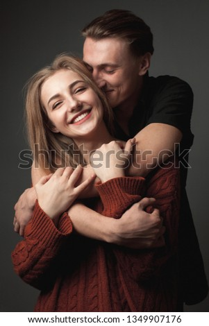 Young woman and young man are hugging and smiling.
